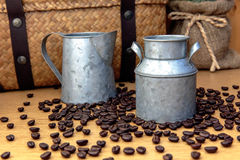 Zinc pot with coffee bean on wooden table. And hamper basket and sack background royalty free stock photos