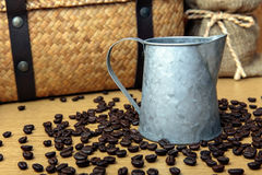 Zinc pot with coffee bean on wooden table. And hamper basket and sack background royalty free stock image
