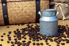 Zinc pot with coffee beans on wooden table. And hamper basket and sack background stock photo
