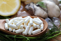 The zinc supplementary white capsule with fresh oyster on block wood Royalty Free Stock Photos