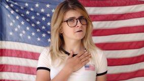 Zingt de blonde jonge vrouw voor Amerikaanse vlag stock videobeelden