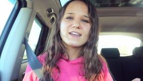 Zingt het tiener mooie meisje en danst in de auto op de zonneschijnachtergrond 3840x2160 stock footage