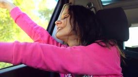 Zingt het tiener mooie meisje en danst in de auto op de zonneschijnachtergrond 3840x2160 stock videobeelden