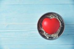 Zinguez le seau avec le coeur rouge sur le fond en bois bleu Photos stock