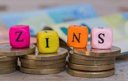 Zins no cubo alemão do alfabeto do interesse no conceito das moedas Fotografia de Stock Royalty Free