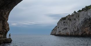 Zinzulusa Caves, near Castro on the Salento Peninsula in Puglia, Italy. Person stands on gang plank at entrance to the caves. Caves of Zinzulusa, near Castro on royalty free stock images