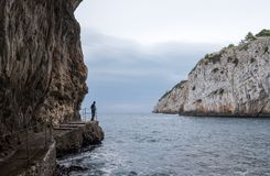 Zinzulusa Caves, near Castro on the Salento Peninsula in Puglia, Italy. Person stands on gang plank at entrance to the caves. Caves of Zinzulusa, near Castro on royalty free stock photos