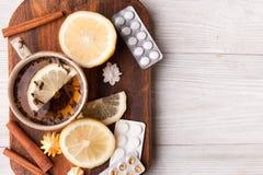 Ziołowa herbata z cytryną i pigułkami być pojęcia ręką opieki zdrowotnej pomoc opóźnioną pigułkę Fotografia Royalty Free