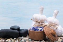 Ziołowi sacs, kamienie dla masażu i zdrój na błękitnym tle zdjęcia stock