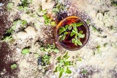 Ziołowy napój taktować niepokój i rozognienie na drewnianej powierzchni w szkle i z całkowitymi surowymi składnikami i ziele zdjęcia stock