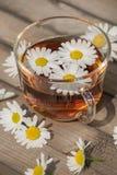 Ziołowa herbata z chamomile na drewnianym stole na lecie pogodny mo Fotografia Stock