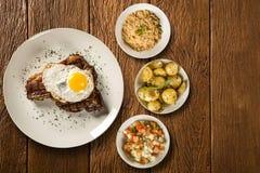 ziobro wieprzowina z jajkiem i bekonem, towarzyszący z nieociosanymi grulami, vinaigrette i kukurydzaną mąką, zdjęcie stock