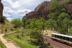 Zion National Park and shuttle bus, Utah. MAIN VALLEY shuttle bus and teenage girl on walking trail Stock Photos