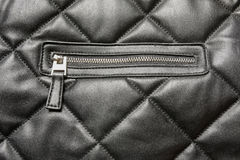 Zip fastener on black quilted leather. Background stock photography