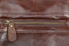 Zip fastener on a brown leather surface close-up. Details of a man`s bag stock photos