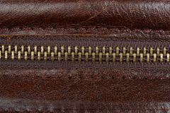 Zip fastener on a brown leather surface close-up. Details of a man`s bag royalty free stock photo