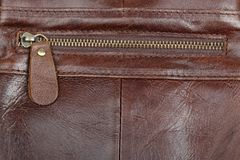 Zip fastener on a brown leather surface close-up. Details of a man`s bag stock photo