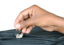 Zip with hand. Detail of zip with hand on a bag with clipping path Royalty Free Stock Images