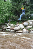 Zip Line. A young girl on a zip line crosses over a river stock photos