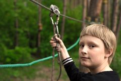 Zip line activity. Boy holding carabiner on zip line in forest, copy space stock photography