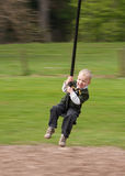 Zip-line Child. Young boy (3.5 years old) on a zip-line. Child is sitting on a zipline seat, with nature (grass and tress) background blurred with panning stock photography