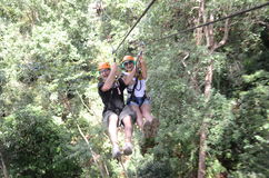 Zip line in Thailand. Tourist going down a zip line in Thailand stock images