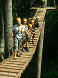 Zip lining on wooden bridge. Zip lining in full gear on wooden bridge stock photography