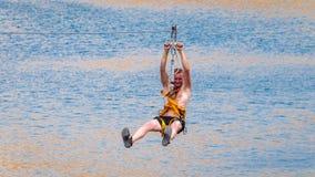 Zipline Mężczyzna w wyposażeniu ono ślizga się na stalowym kablu Tramwaju ślad Nad jeziorem Ekstremum i aktywnego odpoczynek fotografia royalty free