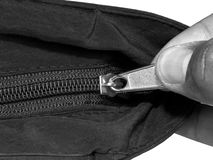 Zipper closing. Close up of hand unzip a bag. Selective focus. black and white texture background Stock Photos