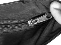 Zipper closing. Close up of hand unzip a bag. Selective focus. black and white texture background Royalty Free Stock Photo