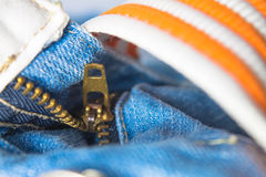 Zipper on jeans with orange and white belt Royalty Free Stock Photo