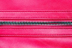 Zipper open between two layers of pink fabric textile and pink leather with visible seam under high magnification close detail stock photo
