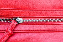 Zipper partly open close up detail photo on a red leather texture background Stock Photo