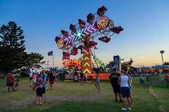 Fairground `Zipper` ride, lit up at sunset royalty free stock image