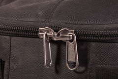Zipper sliders. Two of the zipper slider on the background of dark fabric Royalty Free Stock Photography