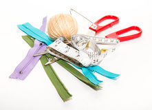 Zippers, centimeter, threads and red scissors on a white backgro Royalty Free Stock Photos