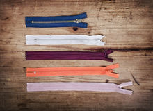 Zippers. Colorful zippers in different sizes over wooden background Stock Photo