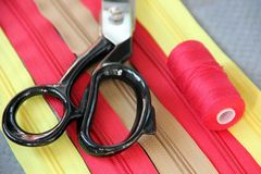 Zippers , scissors and a spool of thread Royalty Free Stock Photos