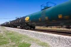 Zipping by dual railroad tracks. Dark green tanker car with yellow markings Royalty Free Stock Photos