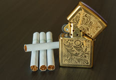 Zippo lighter and cigarettes. Brass metal zippo lighter and cigarettes Royalty Free Stock Image