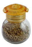 Zira  caraway seeds. Glass jar from the yellow cover filled with caraway seeds on a white background Royalty Free Stock Photos