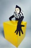 Zirkusart und weisepantomime, der nahe einem gelben Quadrat aufwirft Stockfotografie