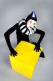 Zirkusart und weisepantomime, der nahe einem gelben Quadrat aufwirft Lizenzfreies Stockbild