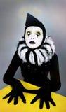 Zirkusart und weisepantomime, der nahe einem gelben Quadrat aufwirft Stockbilder