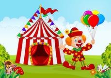 Zirkuszelt mit dem Clown, der Ballon im grünen Park hält Stockfotografie