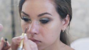 Zit de close-up hoogste mening van een bebouwd kader, een jong mooi meisje met avondsamenstelling als voorzitter van een make-up stock footage