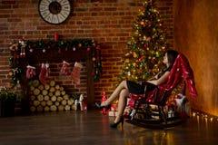 Zit de elegant geklede jonge vrouw in schommelstoel dichtbij Kerstboom Royalty-vrije Stock Foto