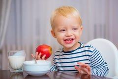 Zit de jong geitje leuke jongen bij lijst met plaat en voedsel Gezond voedsel Jongens leuke baby die de voeding van de ontbijtbab stock foto's