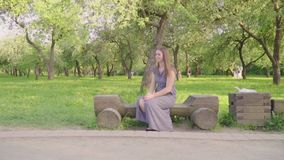 Zit de mooie vrouw van Yong met haar weinig zon op bank in park Langzame Motie stock videobeelden