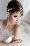 Zit de ochtend mooie gevoelige bruid met kort haar met een zachte kleine kroon op zijn hoofd in een witte zijdelingerie in w Stock Foto's